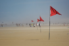 Far away (chris.branruz) Tags: beach flag red sand seaside people wind lacanau france gironde vagues waves sable drapeau gens plage women