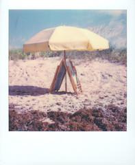 Sunny days (Juliana Longiotti) Tags: beach umbrella sand polaroid polaroidoriginals film instantfilm sx70 northcarolina seaweed sunnyday