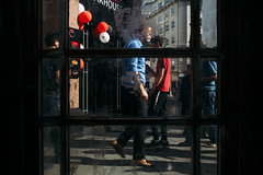 Red, White & Blue (markfly1) Tags: red white blue full colour image balloons floating men walking shirt concierge doorway looking through glass frames within framed bisect lines cross hatching horizontal vertical candid street photo blacks shadows highlighted people nikon d750 35mm manual focus lens