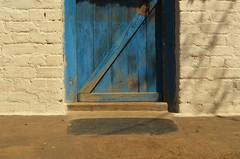 Modest Ingenuity. (Gattam Pattam) Tags: door chhattisgarh threshold shadow sun light wall blue white noon entrance india rural brick wood step texture clean