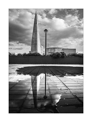 City Slick (Dave Fieldhouse Photography) Tags: monochrome blackandwhite bnw theshard shard skyscraper tower building architecture structure construction sky clouds wet rain pavement reflection reflections lampost wall plants puddle water england london riverthames city citycentre cityscape londonbridge portrait fuji fujixpro2 fujinon wwwdavefieldhousephotographycom streetphotography street