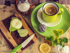 Healthy breakfast. Tea with lemon in a green cup. Near the sugar bowl, a board with a green pear and a knife. Atmospheric photo. Fresh bright colors. Top view. (stok-1707) Tags: background beverage breakfast brown citrus closeup culture cup diet drink flowers food fresh freshness fruit glass green greencolor healthy herb herbal hot ingredient juicy leaf lemon life light liquid natural nature nobody object organic overhead refreshment rustic slice still summer sweet table tea traditional vegetarian vitamin white whitecolor wooden yellow