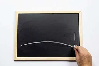 Hand writing with chalk on blackboard