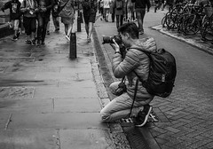 Low point of view.jpg (+Pattycake+) Tags: people camera blackandwhite photographers kneeling street road monochrome crowd city cambridge