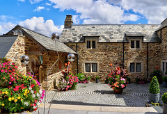 Beautiful Courtyard (Raphooey) Tags: gb uk south west southwest cornwall house mansion court courtyard granite stone stones slate slates cobble cobbles flower flowers flora flowering canna lily lilies begonia begonias petunia petunias cosmos wall walls roof sky cloud clouds hdr