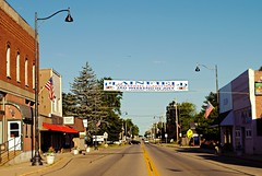 North Street - Plainfield, Wisconsin (Cragin Spring) Tags: smalltown wisconsin wi unitedstates usa unitedstatesofamerica plainfield plainfieldwi plainfieldwisconsin watertower tower wausharacounty building sign flag mainstreet