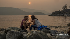 Supper on the Rocks (Moe W) Tags: landscape people rock rocks mountain pacificocean water sky ocean whytecliffpark whyteislet causeway sunset smoke haze sun westvancouver bc canada couple man woman eating supper chopsticks sitting reflection sparkles navigationbouy cliff trees sit seated