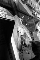 011371 26 (ndpa / s. lundeen, archivist) Tags: nick dewolf nickdewolf blackwhite blackandwhite 35mm film photographbynickdewolf bw january 1971 1970s boston massachusetts candid streetphotography streetlife citylife city downtown people woman women youngwoman youngwomen blond blonde longhair coat subwaystation station mbta mta charlie masstransit sidewalk pedestrians store shop sign storefront arlington hosiery shadow