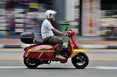 The mobile smoker (jeremyhughes) Tags: singapore street scooter smoker smoking cigarette speed motion moving panning city urban flipflops camopants nikon d7000 nikkor 18200mmf3556 nikkor18200mmf3556gvr helmet visor transport red