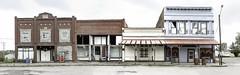 New Hampton, MIssouri (unknown quantity) Tags: abandonedbusiness brokenwindows corrugatedmetal crumblingconcrete utilitypoles wires cloudy rust shadows neglect barrels trees weathered panorama