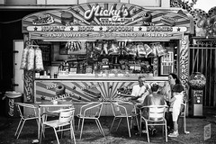 Mickey's Rock & Rolls (Corbicus Maximus) Tags: rockroll chips candyfloss donuts popcorn rock nougat tea coffee dummies hotdogs drinks cocacola sweets burgervan burgers coconutice mickey monochrome blackandwhite nikon d80 18105mm southseauk clarencepier portsmouthuk funfair