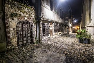 looking down night-time rue de la Prison towards the Vieux Bassin, Musée de la Marine occupying the ancient Église Saint Etienne on the right, Musée d'Ethnographie on the left. Honfleur, Calvados, Normandy, France