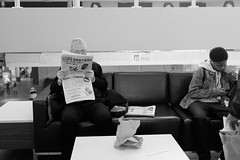 Read and Listen (Michael William Photos) Tags: blackandwhite bw street streetphotography people newyork couch man girl ipod newspaper fujifilm