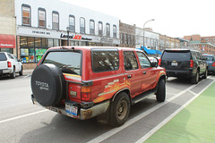 Red Wagon (Flint Foto Factory) Tags: chicago suburb evanston illinois suburban urban college town spring march 2017 downtown 1990 1991 toyota 4runner suv sports utility vehicle sooc straightoutof camera front threequarter view japanese import us market bennisons bakery 1000 davisst maple intersection street parked parking parallel bicycle bike lane new construction road grass lemoi ace hardware store 1008 davis rust red duct tape