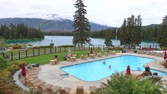 Heated outdoor swimming pool at the Jasper Park Lodge in Jasper, Alberta, Canada (lhboudreau) Tags: lodge resort jasper jasperpark jaspernationalpark alberta canada park nationalpark jasperparklodge fairmontjasperparklodge fairmont outdoor outdoors lawn grass tree trees pine pines sky yard fence lake water beauvertlake lakebeauvert lacbeauvert beauvert mountain mountains canadianrockies rockies chair chairs lounge pool swimmingpool heatedswimmingpool heatedpool heated swimming landscape people forest umbrella umbrellas