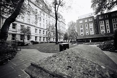 Postman's Park (goodfella2459) Tags: nikonf4 afnikkor14mmf28dlens fujifilmneopan400cn 35mm c41 blackandwhite film analog postmanspark london park trees buildings city bwfp
