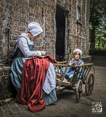 Tudor Mother and Daughter (Cunobelin2) Tags: tudor mother daughter brick house cart sewing red cloth childfamily trees beams history staring bonnet stitching needlework