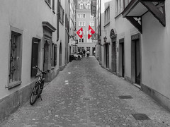 Zurich Old Town (Anthony Kernich Photo) Tags: zurich monochrome switzerland swiss town travel lumix olympus mono street road city grayscale key europe one coloring flickrheroes urban streetscape selectivecolor microfourthirds flag swissflag alley alleyway narrow perspective object blackandwhite bw blackwhite