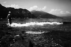 The Wave (stefankamert) Tags: wave woman lake lakecomo mountains clouds grain noir blackandwhite blackwhite stefankamert water stones comersee bellagio gr grii bw baw landscape sun italy sky ricoh
