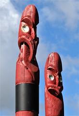 Kerikeri, Bay of Islands, NZ - Pouwhenua (zorro1945) Tags: kerikeri nz bayofislands northisland newzealand pouwhenua totempoles poles carvings maoricarvings maoriculture history flickrtravelaward faces red