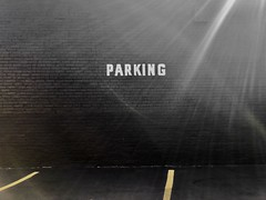 Parking (Crawford Brian) Tags: parking sign painted brick black yellow carpark parkinglot berwyn illinois sun flare asphalt building