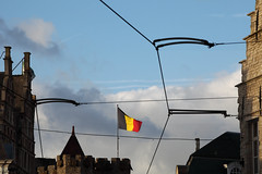 Tramsversing (Elios.k) Tags: horizontal outdoors nopeople stone walls buildings houses street flag belgianflag sunlight tramlines cables powerlines dof depthoffield focusinbackground foregroundblur frame keep tower towers castle gravensteen medieval architecture building sky bluesky clouds cloudy weather colour color travel travelling november2017 canon 5dmkii photography ghent gent belgium belgique flanders flemishregion europe