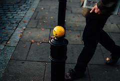 Newsprint (ewitsoe) Tags: 35mm city cityscape nikond80 street warszawa erikwitsoe pedestrians summer urban warsaw low dof newspaper man hand pole yellow cinematic sidewal walking legs feet hands coat