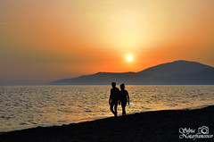 A couple in the setting sun. (TatiAppleHead) Tags: sun sunset sea seaside orange yellow grey blue beach mountain couple love lovely passion nikon nikond5100 d5100 dark light photo picture photography peace calm ascea italy italia campania salerno