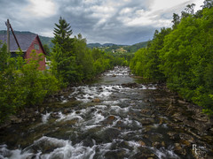 The River in Rosendal (RobertCross1 (off and on)) Tags: 1250mmf3563mzuiko em5 europe hordaland longexposure melselva norge norway omd olympus rosendal scandinavia barony building clouds creek fjord forest landscape river stream town trees village water