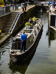 Perfect Positioning (Steve Taylor (Photography)) Tags: lock canal boat steering architecture man woman lady uk england london camden gb greatbritain plants reflection ripples