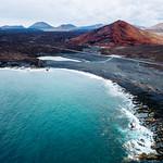 Red volcanic mountain in front of the ocean / Roter vulkanischer Berg vor dem Ozean thumbnail