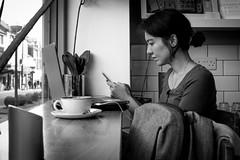 Townhouse candid (Chilanga Cement) Tags: fuji fujix100f fujifilm bw blackandwhite monochrome lady girl cafe candid phone reading