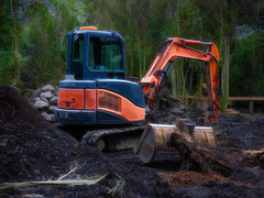 Making Mud Pies (Steve Taylor (Photography)) Tags: digger excavator jcb digitalart building construction blue orange brown green rock newzealand nz southisland canterbury christchurch trees root trunk texture shovel scoop