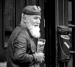 A Scotsman with a Peroni (Clare-White) Tags: man edinburgh drink holding glass beard outside candid hat glasses face bw