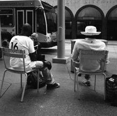 untitled (kaumpphoto) Tags: rolleiflex tlr 120 ilford bw black white bus street urban city hat 16 minneapolis nicolletmall nicollet chair arch awning pavement sidewalk pole brick wall humbolt backpack bag men back
