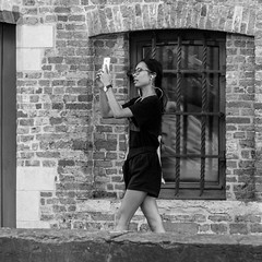 tourism in the 21st century (every pixel counts) Tags: 2018 belgium bruges bricks europa street woman girl everypixelcounts blackandwhite smartphone mobiledevice bw square blackwhite window cellularphone people belgië earphones 11 eu brugge tourist sightseeing