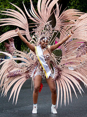 Nottingham Carnival 2018 (englishreader) Tags: nottinghamcarnival nottinghamcaribbeancarnival nottingham costume colour color colors colourful colorful brightcolours brightcolors entertainment entertainer performer naturallight daylight availablelight people person feathers happy smile smiling headdress brown white yellow red girl girls female youngwoman younglady