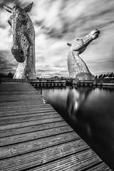 "fine art black & white long exposure, ND filter, of The majestic Kelpies towering over the Forth & Clyde Canal, Falkirk, Scotland, UK (grumpybaldprof) Tags: canon 7d ""canon7d"" sigma 1020 1020mm f456 ""sigma1020mmf456dchsm"" ""wideangle"" ultrawide bw blackwhite ""blackwhite"" ""blackandwhite"" noireetblanc monochrome ""fineart"" ethereal striking artistic interpretation impressionist stylistic style ""longexposure"" ""neutraldensity"" nd ""thekelpies"" horsehead sculpture forth clyde canal ""rivercarron"" ""thehelix"" scotland uk ""andyscott"" statues 2013 ""forthclydecanal"" ""riverforth"" steel ""stainlesssteel"" ""30mtall"" ""300tonnes"" art artist mythology ""heavyhorse"" reflections water clouds movement mood moody atmosphere atmospheric horses horseheads drama magnificent huge"