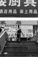 To the mystery (Go-tea 郭天) Tags: qingdaoshi shandongsheng chine cn qingdao huangdao shandong stairs steps up upstairs climb climbing movement man alone lonely dirty dirt mess messy shops business mystery surprise back backside street urban city outside outdoor people candid bw bnw black white blackwhite blackandwhite monochrome naturallight natural light asia asian china chinese canon eos 100d 24mm prime