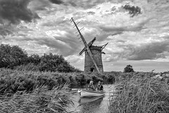 Homeward Bound in B&W (Electric Gnome) Tags: bw water river women rowing nikon d850 1635mm norfolk eastanglia windmill rural england clouds derelict reeds brograve