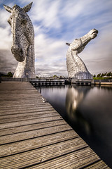 """fine art colour long exposure, ND filter, view of The Kelpies towering over the Forth & Clyde Canal, Falkirk, Scotland, UK (grumpybaldprof) Tags: """"thekelpies"""" horsehead sculpture forth clyde canal """"rivercarron"""" """"thehelix"""" scotland uk """"andyscott"""" statues 2013 """"forthclydecanal"""" """"riverforth"""" steel """"stainlesssteel"""" """"30mtall"""" """"300tonnes"""" """"fineart"""" ethereal striking artistic interpretation impressionist stylistic style contrast shadow bright dark black white illuminated """"longexposure"""" """"neutraldensity"""" nd canon 7d """"canon7d"""" sigma 1020 1020mm f456 """"sigma1020mmf456dchsm"""" """"wideangle"""" ultrawide horses reflections clouds sky time towering art artist mythology """"heavyhorse"""""""