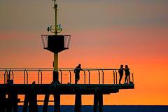 Waiting for the sunrise (Fnikos) Tags: sea water mar mare people pont pier puente sky cloud skyline sun sunrise sol light lighhouse faro amanecer dawn outdoor