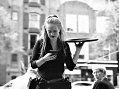 Candid of a Waitress (d_t_vos) Tags: waitress woman youngwoman girl teenager portrait candid outside terrasse contrast monochrome dof people buildings phone cell cellphone tray plate servingtray blond blonde groningen hogedera bommenberend groningsontzet 28augustus achtentwintigsten dickvos dtvos