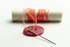 Red button with orange thread on a spool (wuestenigel) Tags: repair color spool sewing thread button tailoring orange red needle nadel noperson keineperson yarn garn isolated isoliert bobbin spule nähen needlework handarbeit closeup nahansicht sharp scharf desktop farbe paper papier stilllife stillleben tool werkzeug medicine medizin wood holz fashion mode string zeichenfolge equipment ausrüstung craft kunst
