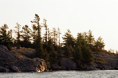 across the channel (.grux.) Tags: asahipentaxsv supertakumar135mmf35 m42 film kodakgold200 settingsun light water channel island rock trees reflection sunnyf16 georgianbay