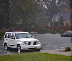 Flooding Parking Lot. (dccradio) Tags: lumberton nc northcarolina robesoncounty outdoor outdoors saturday evening latesummer earlyfall earlyautumn september tree trees foliage greenery leaf leaves treebranch branch branches treebranches parking parkinglot paved pavement flooding hurricane florence hurricaneflorence storm rain raining rainy flood floods weather weatherevent nature natural sky cloudy overcast lines paintedlines standingwater water bodyofwater floodwater nikon d40 dslr jeep suv shrub bushes