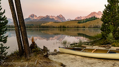 Canoe parked on the shore of an Idaho mountain lake at sunrise (The Knowles Gallery) Tags: blue forest grass green idaho lake mountains nature outdoors plants reflection sawtooths sky sunrise trees water wilderness canoe