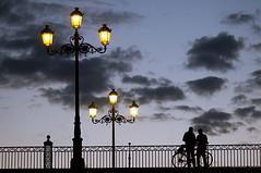 (ale arillo) Tags: sevilla andalucía andalusia puentedetriana triana puente baranda siluetas contraluz nubes color luz luces farol farolas bicicleta personas compañía cielo gente nikon d300