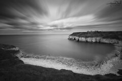 Solitary Figure on Thornwick Bay (AndyNeal) Tags: landscape seascape cliffs water sky beach blackandwhite monochrome longexposure neutraldensityfilter movement cloudmovement watermovement milkywater milkysea flamborough thornwickbay thornwick bay caves sea