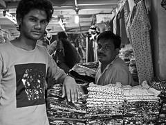 Not a mannequin (magiceye) Tags: street streetphoto streetportrait shopkeeper salesman lalbaug monochrome blackandwhite mumbai india textiles display